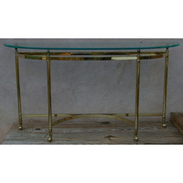 Both modern and traditional, this glamorous polished brass console table adds glamour to an entry or hall. It is even...