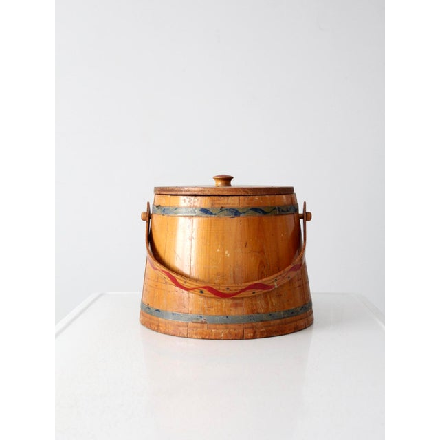 This is an antique sugar bucket. Hand-painted folk art flowers adorn the wooden barrel style basket. It features a wooden...