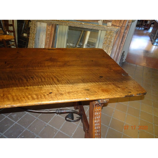 19th century walnut Spanish table with hand forged iron trestle. One solid walnut plank table top. Front of legs are...