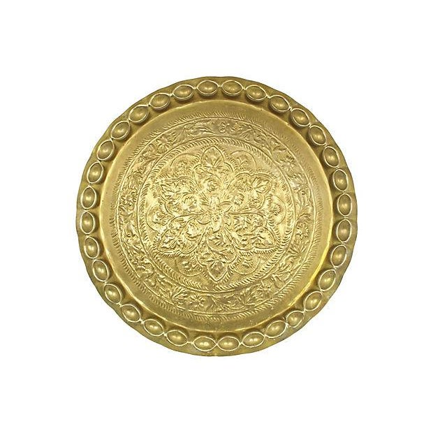 Moroccan brass tray with repousse motif thumbprint rim detail. Hardware on back to allow tray to be hung on the wall. No...