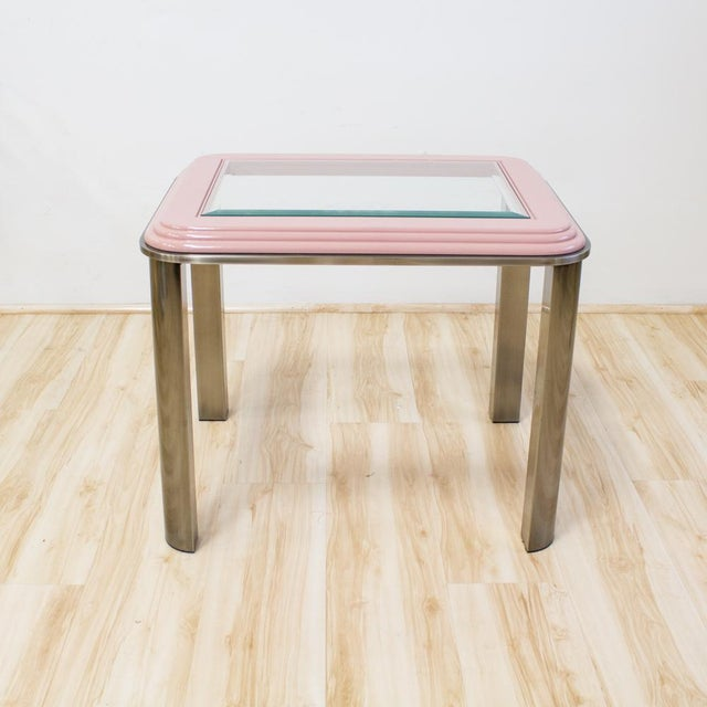 Memphis style side table in pink and chrome labeled 'DIA Design Institute of America 1986' features a glass top cased in a...