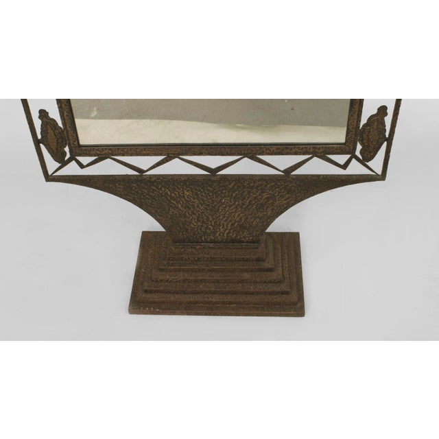 French Art Deco wrought iron cheval mirror with an arch form top and open filigree border resting on a tiered rectangular...