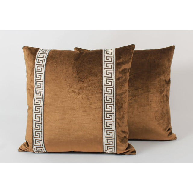 Pair of custom coffee color velvet pillows with coordinating chocolatel-and-ivory colored Greek key tape on fronts. Solid...
