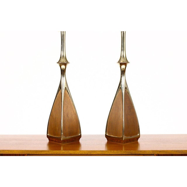 Nice pair of large vintage table lamps by Laurel. Cast brass body with walnut detailing. Sculptural form. Great vintage...