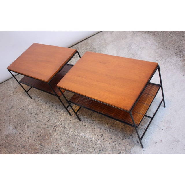 Pair of Paul McCobb occasional / end tables composed of painted wrought iron frames, solid maple tops, and slatted rattan...