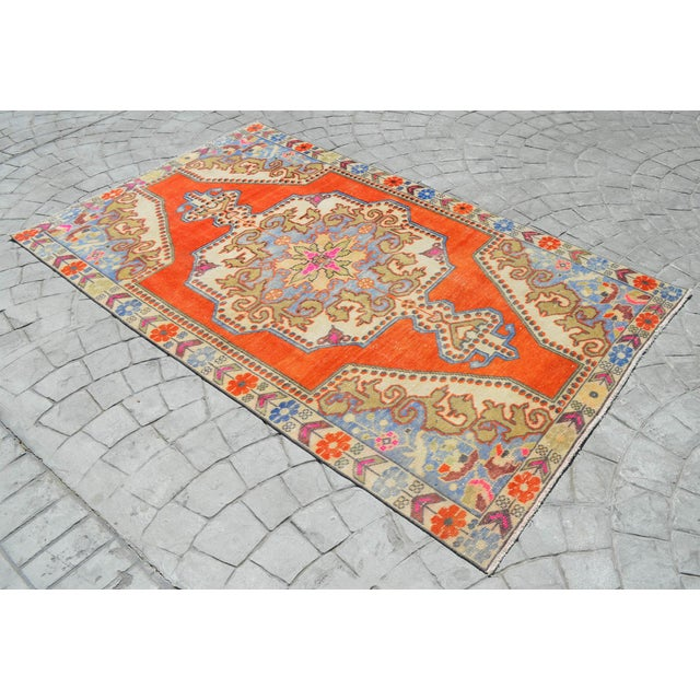 This is a beautiful vintage hand knotted distressed finish Rug from Turkey. It has bright primary colors on a light...