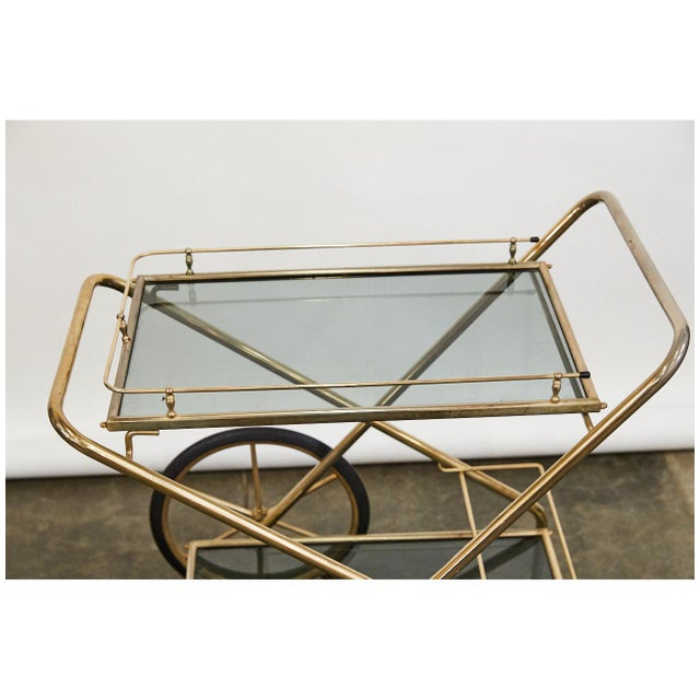 This classic bar cart is beautifully designed with grey glass shelves that sit in the bright brass frame. The cart has two...