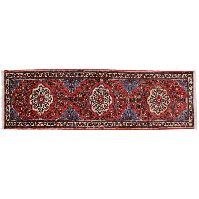 Hand-knotted wool vintage Persian Rudbar runner featuring three medallions with an allover floral pattern surrounded by a...