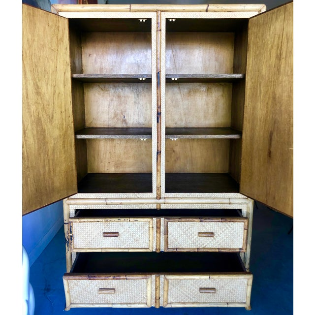 Vintage burnt bamboo/rattan armoire. Sunburst designs on the front and side panels. 2 drawers below, 3 shelves inside....