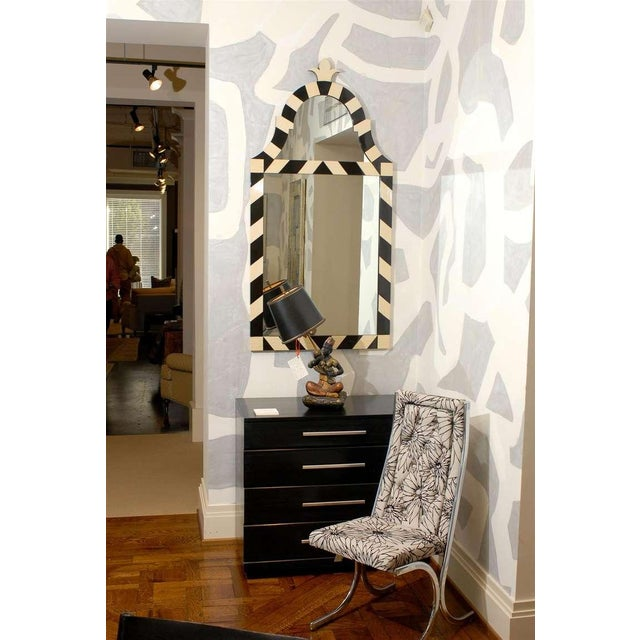 An Exceptional pair of modern High Style wood mirrors in black and cream lacquer, circa 1970's. The unusual frames are...