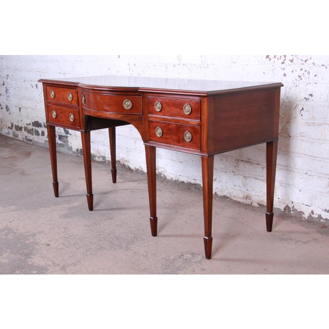 A gorgeous antique Hepplewhite style mahogany sideboard or buffet server. The sideboard features beautiful mahogany wood...