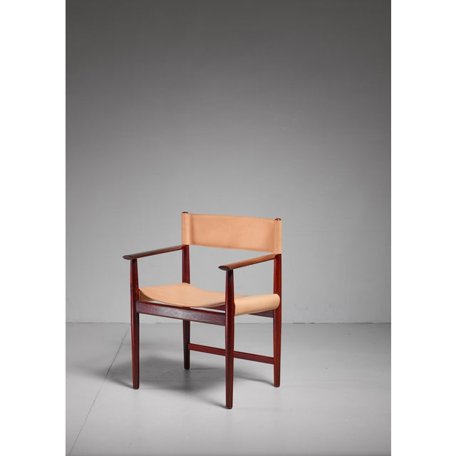 A rosewood armchair with a natural leather seating and backrest, by Kurt Østervig for Sibast. The chair has been...