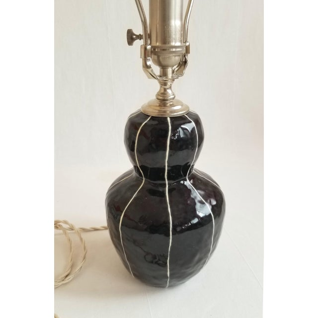 Handmade ceramic lamp glazed in glossy black with raised white stripes. Just the right size and shape to be a bedside...