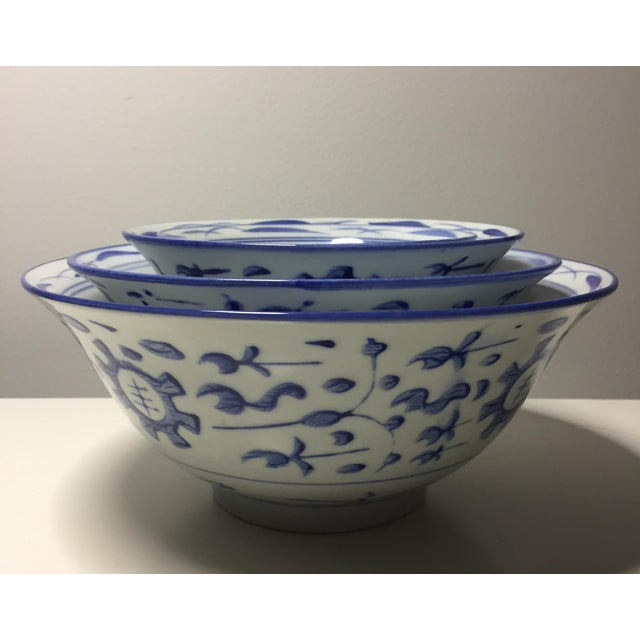 Stacked set of four Chinese porcelain bowls with blue and white decoration. No cracks, chips, or visible damage. However...