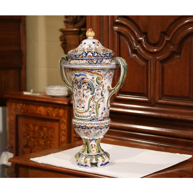 This elegant antique vase was created in Rouen, France. Crafted circa 1850, the colorful, ceramic vessel features a cone...