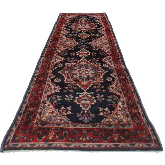 Crafted of hand-knotted wool, this Persian Kerman runner features an all-over floral design.