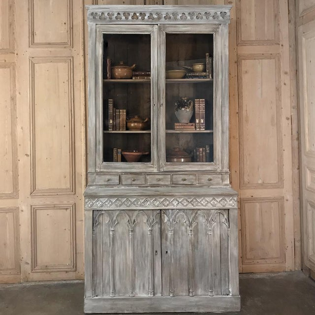 19th Century French Gothic Whitewashed Bookcase features intricately carved trefoil and moorish arch detailing, with...
