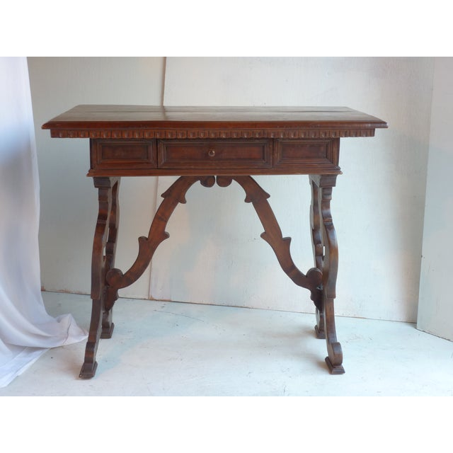 19th-century Italian Renaissance-style walnut console with chip carved edge, single drawer with iron handle. Some scuffs,...