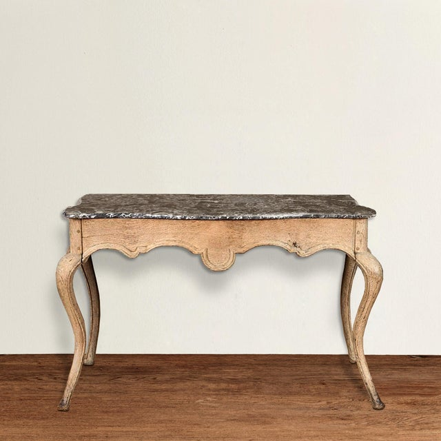 An incredible ornamental yet not ostentatious 19th century French Louis XVI-style unfinished oak console table with a...