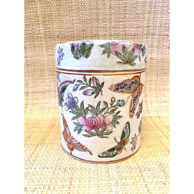 Handprinted porcelain lidded container adorned with flowers and butterflies. Place on a bookshelf, on a stack of art...