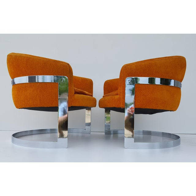 Iconic Pair of 1970s Milo Baughman attributed orange barrel back chairs with flat bar chrome bases, and button tufted...