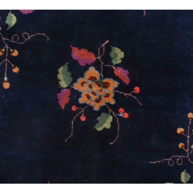 An early 20th century Chinese Art Deco rug with a beautiful indigo background with an all-over, symmetrical, multicolored...