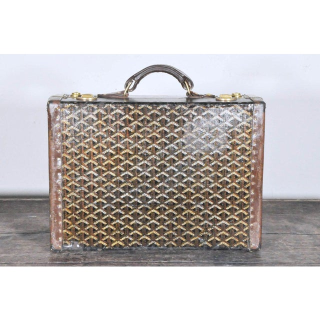 A 19th century hardside Goyard suitcase. Custom monogramming and wear from long ago travels inspire musings about the...