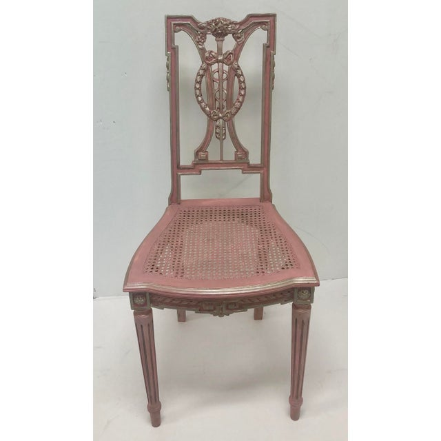 F. Louis XVI style chair with hand carved wooden elements and caned seats. Painted pink with silver accents on the high...