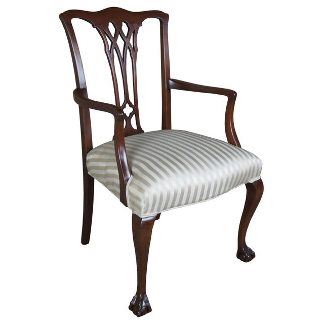 Beautiful antique chippendale style mahogany arm chair. Features dark wood and striped cushion.