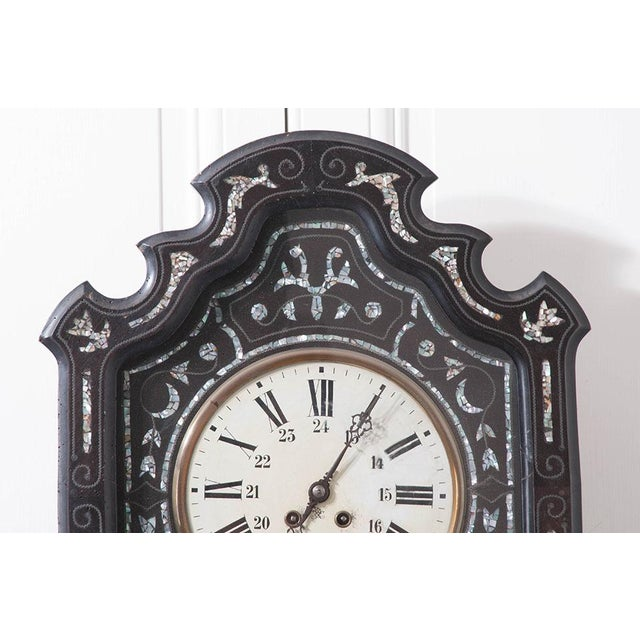 This 19th century clock is stunning with its rippling, shaped clock frame of ebonized wood. Mother of pearl designs are...