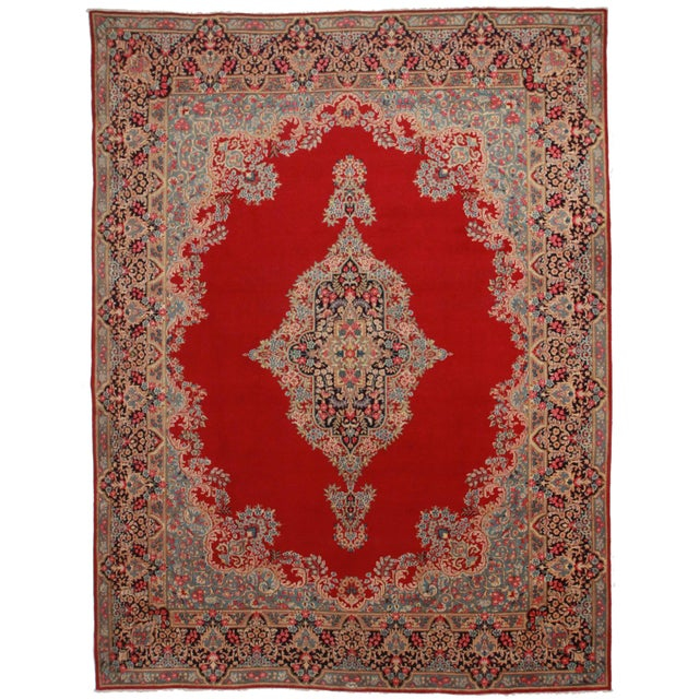 Here is a vintage Persian Kerman rug. Made of hand-knotted wool. Red background with a medallion design.