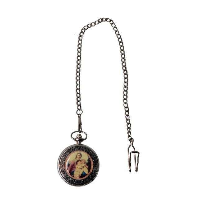 Round Shape lady and baby hugging painting pocket wall, this watch is operated by winding the spring knot on the top. it...