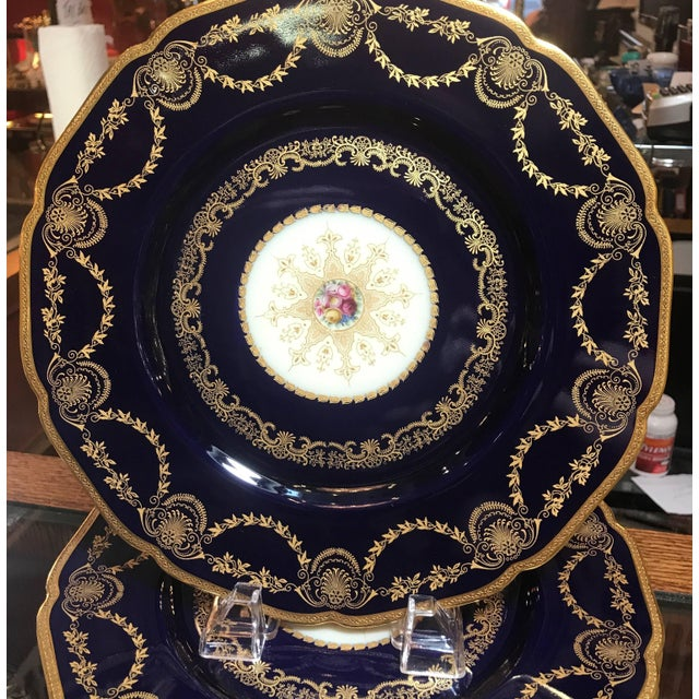 Elegant and opulent deep cobalt blue service plates. The rich borders with gilt swags and borders with a center gilt...