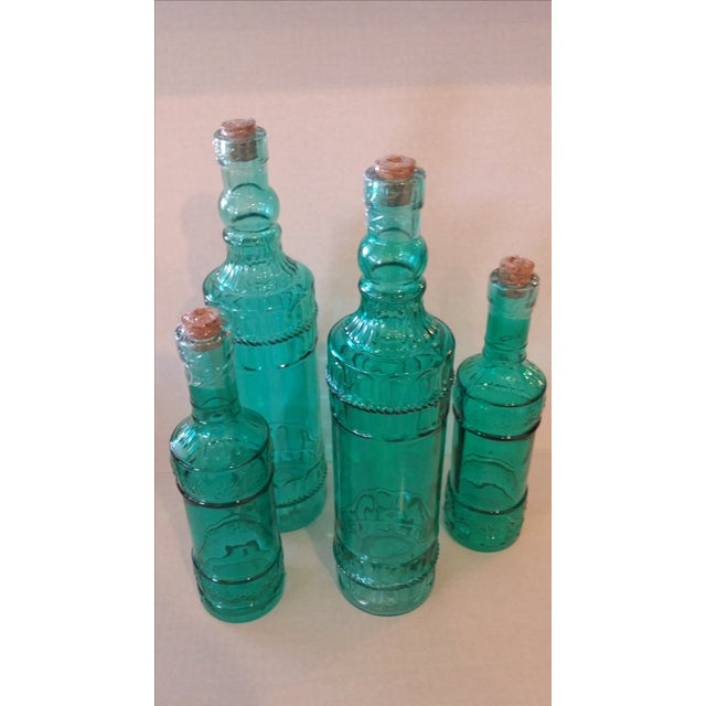 Set of four bottles in turquoise glass. Great as an accessory in your home or can even be used as vases. Cork tops. Large:...