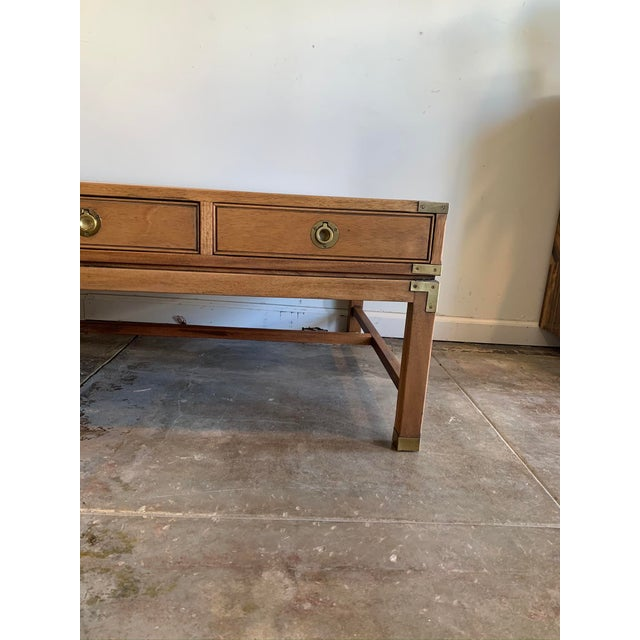 Handsome and well sized, this oak wood campaign-style coffee table offers three practical drawers on one side and brass...