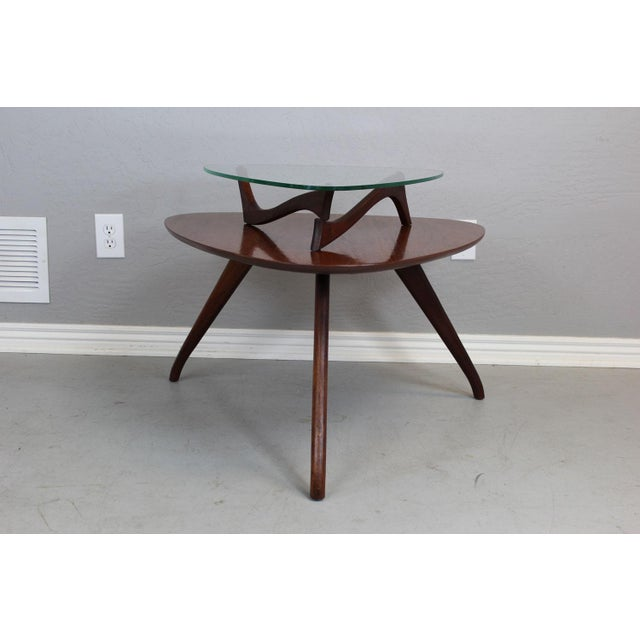 Crafted of mahogany and walnut, this two-tier side table in the style of Vladimir Kagan. Professionally restored.