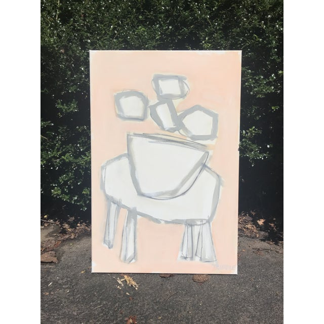 Simple shapes outlined in soft neutral gray on a pale peachy pink background form a balanced, abstracted composition of a...
