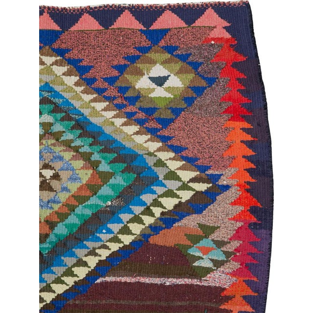 A vintage Persian flat-woven Kilim rug from the mid-20th century. A Kilim is a flat tapestry-woven carpet or rug...