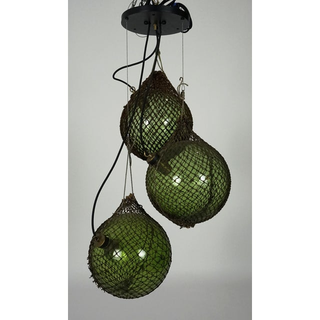 A pendant light made from three, large, green glass, float spheres from Japan, with the original netting used for fishing....