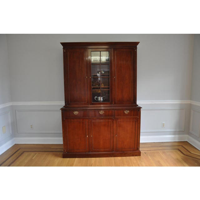 A traditional style cabinet with flame mahogany and bubble glass breakfront custom made in Argentina, circa 1989. The...