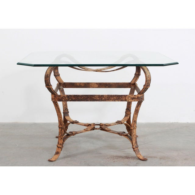 An elegant iron table base created as though it were made of equestrian leather harness straps, rings and buckles are...