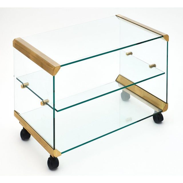 Italian modernist glass and brass side table with one glass shelf and supported by casters. The glass structure is held...