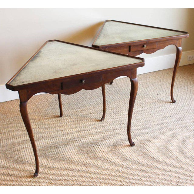 An unusual pair of 1940s Italian triangular-shaped tables with elegantly carved legs and skirts each fitted with a drawer...