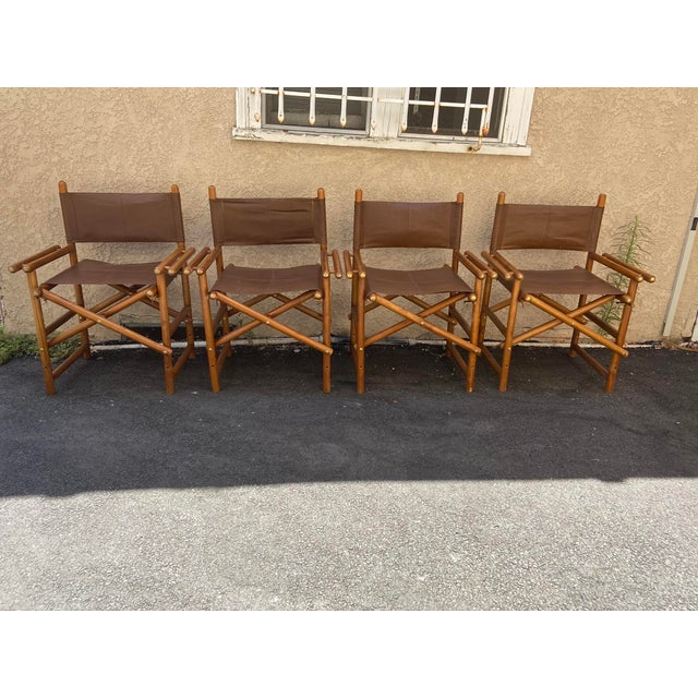 This set of 4 Safari leather chairs is in wonderful vintage condition with brass hardware and patina consistent with age....