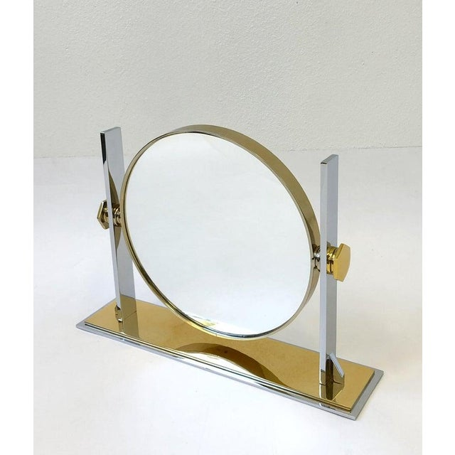 A spectacular polish brass and polish nickel vanity mirror designed by Karl Springer in the 1980s. The mirror can be...