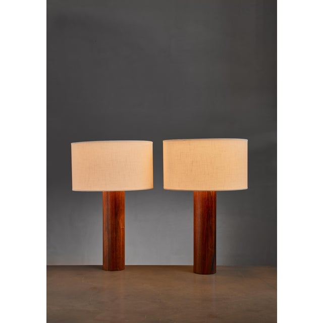 A pair of cylindrical, wooden table lamps by Uno & Östen Kristiansson for Luxus. Labeled by Luxus. The measurements stated...