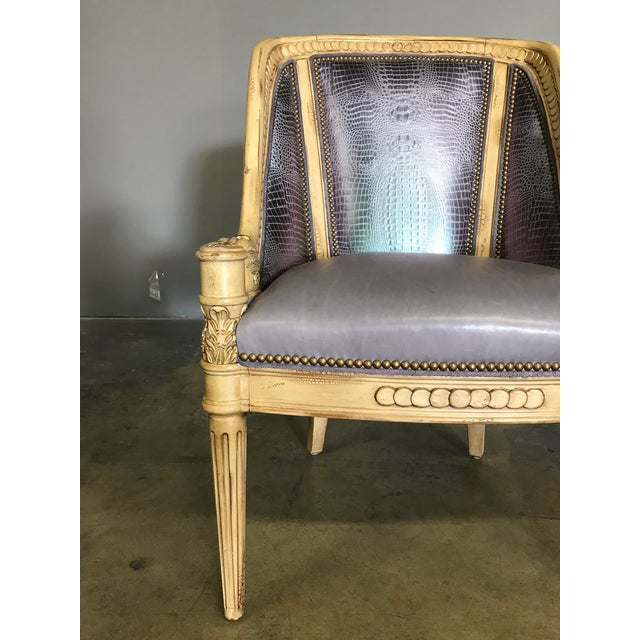 Carved lounge chair with metallic embossed leather upholstery, suede piping, and nail heads.