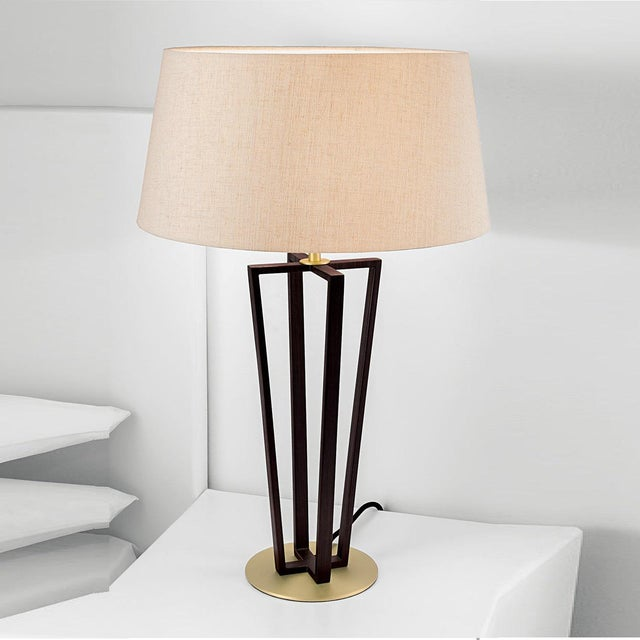 Geometric design black bronze with antique brass accents table lamp and shade. The lamp stands on a flat circular brass...