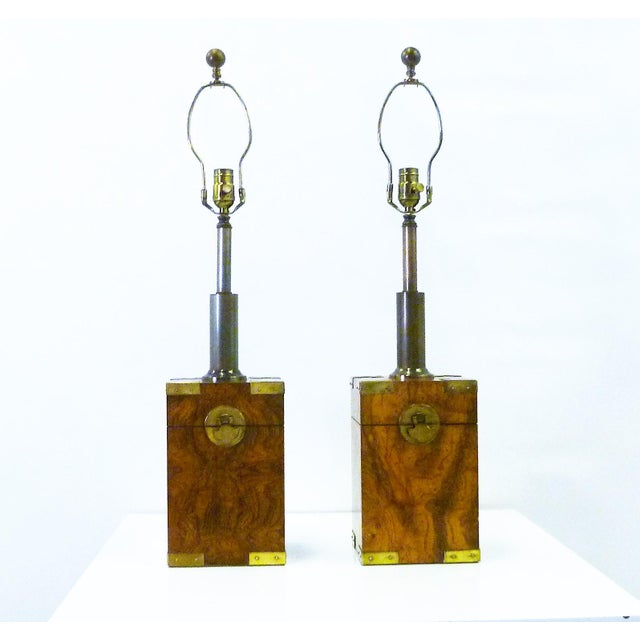 Beautiful burl woods and brass campaign style mounts highlight this pair of table lamps. Depicting antique tea boxes, they...