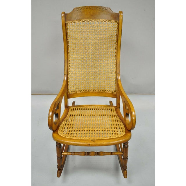 Antique Eastlake Victorian Cane & Maple Wood Primitive Rocking Chair. Item features hand caned back and seat, solid wood...